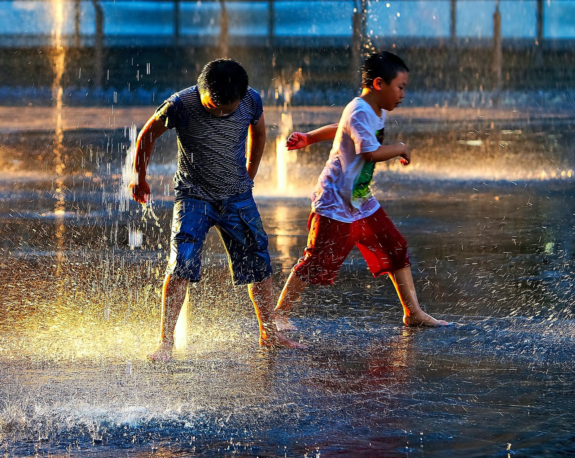 公園の噴水で遊ぶ子供たち